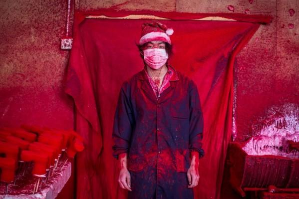 """Ο 19χρονος Wei δουλεύει σε εργοστάσιο της Yiwu στην Κίνα. """"Ντύνει"""" με κόκκινο χρώμα πολυεστερικές νιφάδες χιονιού."""