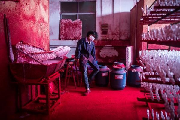 Ο Wei χρησιμοποιεί περί τις 10 μάσκες ημερησίως προσπαθώντας να μην αναπνέει – όσο μπορεί- το σύννεφο της κόκκινης μπογιάς.