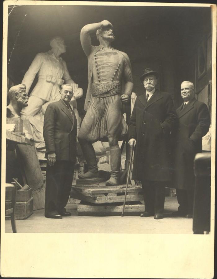 Ο πρίγκιπας Γεώργιος με τον γλύπτη Γ. Κανακάκη. Πίσω του το γλυπτό του Μνημείου της Μεταπολιτευτικής Επιτροπής, που εγκαινιάστηκε στις Βρύσσες Αποκορώνου στις 2 Μαΐου 1954.