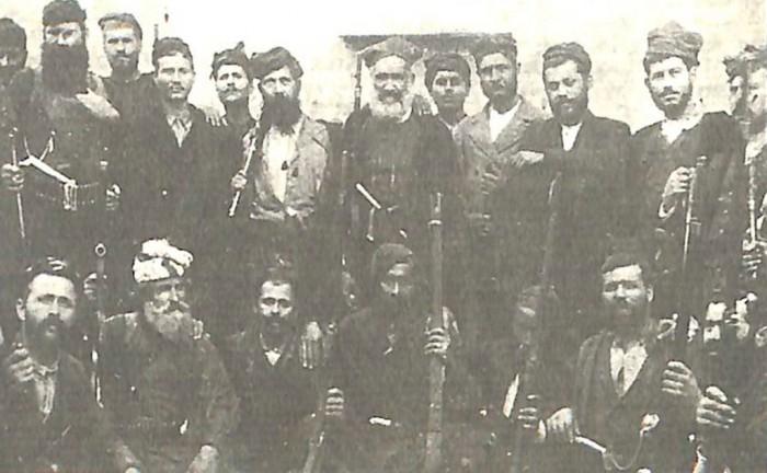 Επαναστάτες με μέλη της Μεταπολιτευτικής Επιτροπής (Πιθανότατα η φωτογραφία ελήφθη αμέσως μετά την πολιορκία του Βάμου). Καθιστοί από αριστερά προς τα δεξιά: 1ος Ιωάννης Γενεράλης από Γερακάρι Αμαρίου Ρεθύμνης, 2ος Αναγνώστης Κουρής ή Κουρινάκης από Αλίκαμπο Αποκορώνου, 3ο2 Ιωσήφ Γ. Λεκανίδης από Αλίκαμπο Αποκορώνου, 4ος Ο ήρωας Παπα-Μαλέκος από Βάμο Αποκορώνου Όρθιοι από αριστερά προς τα δεξιά: 2ος Σταυρούλης Ζουρίδης από Ασκύφου Σφακίων, 4ος Γεώργιος Μ. Μυλωνογιάννης από Κεφαλά Αποκορώνου, 5ος Εμμ. Μουντάκης από Κεφαλά Αποκορώνου, 6ος Στυλιανός Φωτάκης από Μέλαμπες Αγίου Βασιλείου Ρεθύμνης, 7ος Κων/νος Μαλινός από Γαβαλοχώρι Αποκορώνου, 9ος Γεώργιος Σκουλάς από Ανώγεια Μυλοποτάμου Ρεθύμνης, 10ος Μάρκος Δημητρακάκης από Ροδάκινο Αγ. Βασιλείου Ρεθύμνης, 12ος Εμμαν. Φραντζεσκάκης από Βάμο Αποκορώνου.