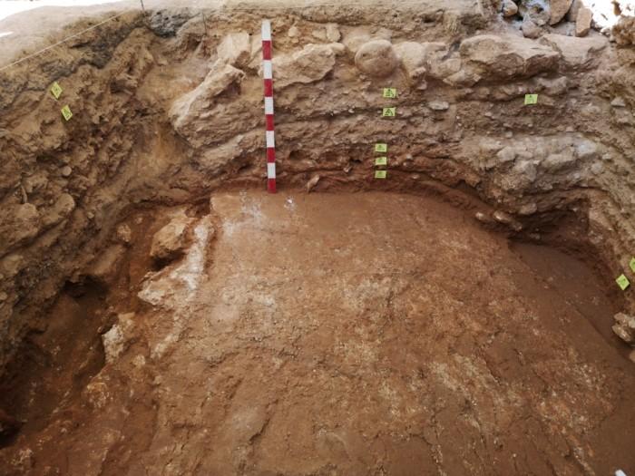 Δυτική παρειά τάφρου ΙΗ. Όψη της στρωματογραφίας, στην οποία αποτυπώνεται καθαρά η κατακρήμνιση των στρωμάτων και των δομών (αρχαϊκού τοίχου και μυκηναϊκού δαπέδου) μέσα στο ρήγμα.
