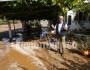 Ο Ευτύχιος Φραγκέδης και η Μαριάννα Πατσουράκη καθαρίζουν την αυλή του καφενείου  στην Κουντούρα από  τις λάσπες.